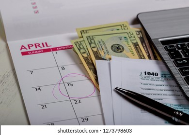 1040 US tax form, money and calendar with U.S dollars money and computer