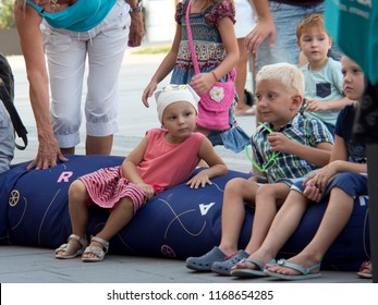 10.august 2018, Trnava, Slovakia The children sit on the inflatable mattress on the city street and wait for a theater performance that is organized by the city office during their holidays.