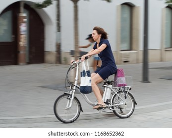 10.august 2018, Trnava, Slovakia A woman sits on an electric bicycle and swiftly moves across the street of the city.