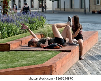10.august 2018, Trnava, Slovakia Young girls relax on a wooden mat in the square. One of them is lying down and pointing to a floral planting behind her head.