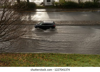 10th November 2018- A car being driven through flood water on a road next to the river Towy in the town centre of Carmarthen, Carmarthenshire, Wales, UK.