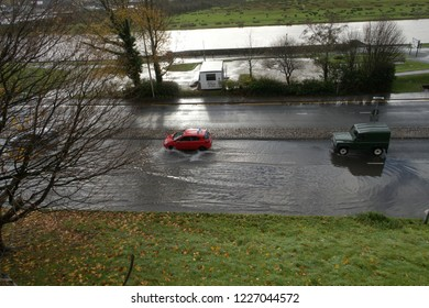 10th November 2018- Cars driving through flood water on a road next to the river Towy in the town center at Carmarthen, Carmarthenshire, Wales, UK.