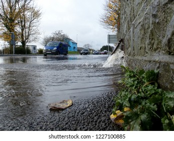 10th November 2018- Water flowing out of a drain and flooding the road near the river Towy, after very heavy rain, in the town center at Carmarthen, Carmarthenshire, Wales, UK.