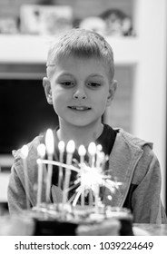 10-year-old Caucasian boy blowing out candles on cake