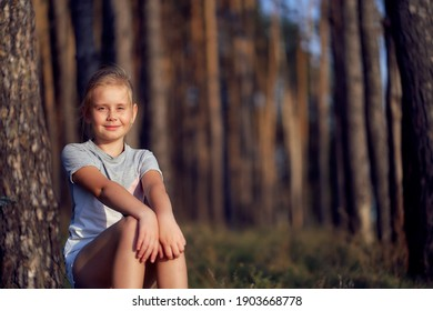 A 10-year-old girl sits on nature by a tree in a pine forest on a warm summer day.