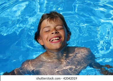 a 10-years old laughing American - German boy having fun with diving and swimming in a swimming pool, photographed in the summer sun
