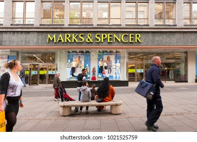 11 April 2011: Sheffield, South Yorkshire, UK - Shop window and sign of Marks and Spencer, Fargate, Sheffield, people walking by and sitting on bench. Slight motion blur on foreground people.