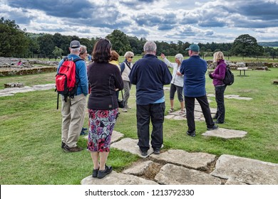 11 August 2018: Northumberland, UK - Visitors listening to a guide on a tour at Chesters Roman Fort, Hadrian's Wall, Northumberland, UK