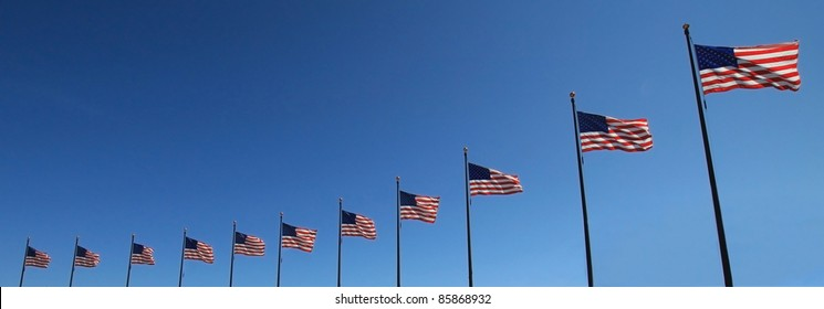 11 flags in a row with a beautiful blue sky