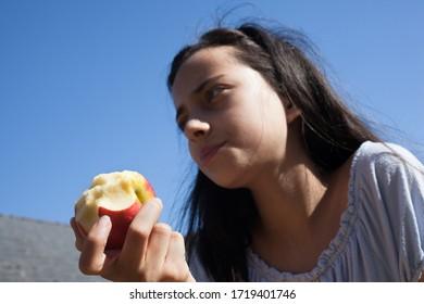 An 11 year old girl eating an apple