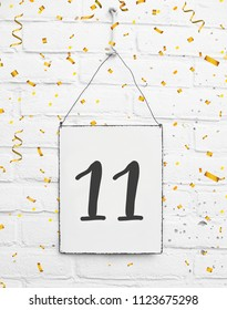 11 years old birthday party card text with golden confetti, number eleven, metal plate white brick background