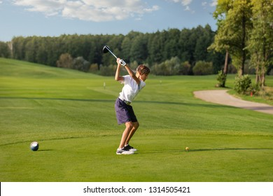11 years old boy golfer hitting by iron from tee at golf course