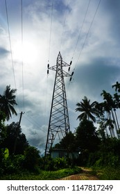 110 KV steel electricity transmission tower in a remote village in India, against dark blue sky.