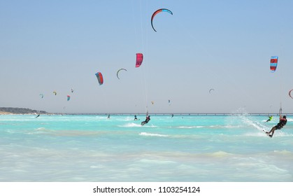 11.06.2017. the paradise beach with a turquoise sea and blue sky and people who practice kite surf in the middle of the waves, Rosignano Livorno, Italy