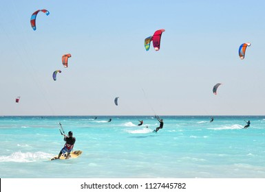 11.06.2017. the paradise beach with a turquoise sea and blue sky and people who practice kit surf in the middle of the waves, Rosignano Livorno, Italy