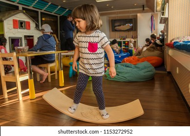 11.07.2018 Liner Stokholm-Riga. A little girl is swinging on a curved swing board. Wooden board that helps children develop the vestibular system and kinesthetic perception.