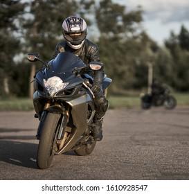 11-08-2019 Riga, Latvia. Woman in black leather jacket ride on black sport motorcycle.   Suzuki motorcycle