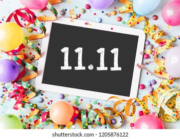 11.11 on a school slate with colorful carnival frame of multicolored balloons, confetti, candy and twirled streamers in a conceptual image
