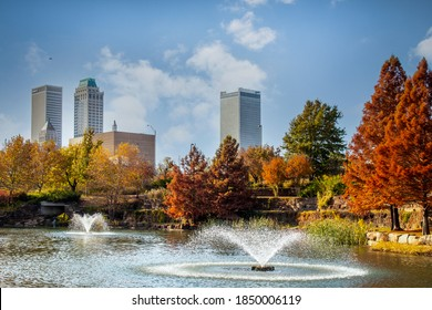 11-16 2020 - Tulsa USA - View from Central Park of downtown Tulsa Oklahoma on bright autumn day with colorful foliage and lake and fountains in foreground and vintage skyscrapers behind