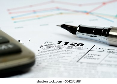 1120 tax forms closeup with calculator and colorful charts