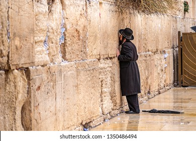11/23/2018 Jerusalem, Israel, Believing Jew is praying near the wall of crying in a big black hat and kiss the wall