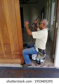 11.4.2021, Lundang Paku, Kelantan, Malaysia: a man is doing work punching a hole in a main house door