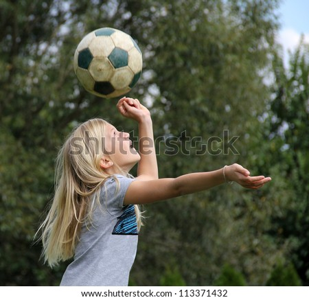11-year old blond girl playing with a football, reaching to head the ball