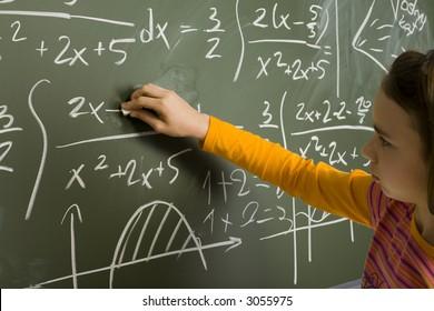 11yo girl are writting maths using chalk on greenboard.