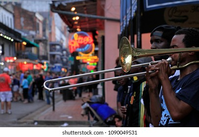 12 April 2017 - New Orleans, Louisiana: Jazz musicians performing in the French Quarter of New Orleans, Louisiana, with crowds and neon lights in the background.