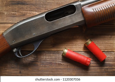 12 gauge pump action shotgun on wood detail and shells.