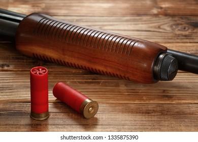 12 gauge pump action shotgun and shells on wood.