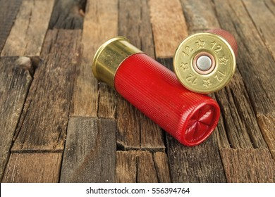 12 gauge red hunting cartridges for shotgun on wooden background. Macro shot.