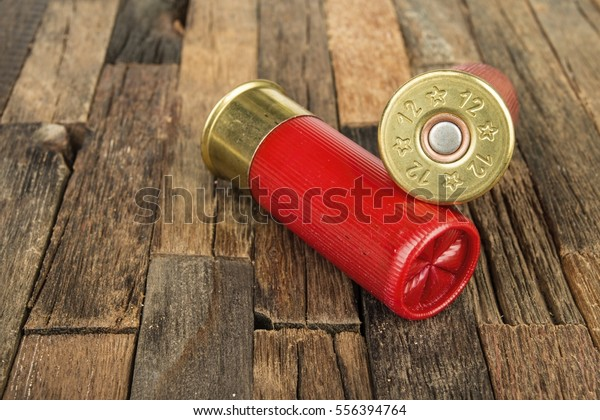12 gauge red hunting cartridges for shotgun on wooden background. Macro shot.