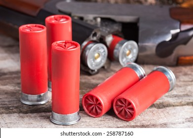12 gauge shotgun shells with shotgun on wood surface