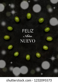 """12 grapes in the shape of a clock and bokeh. """"Happy New Year"""" text in Spanish. Spanish tradition concept of eating 12 grapes on New Year's Eve"""