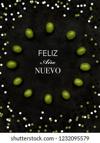 "12 grapes in the shape of a clock with confetti. ""Happy New Year"" text in Spanish. Spanish tradition concept of eating 12 grapes on New Year's Eve"