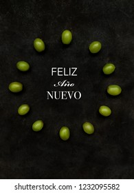 "12 grapes in the shape of a clock. ""Happy New Year"" text in Spanish. Spanish tradition concept of eating 12 grapes on New Year's Eve"