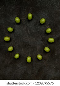 12 grapes in the shape of a clock on textured black background. Spanish New Year's Eve Concept.