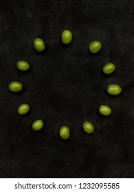 12 grapes in the shape of a clock on black background. Spanish New Year's Eve Concept