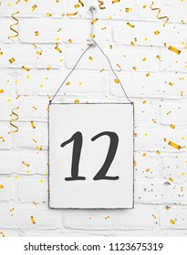 12 years old birthday party card text with golden confetti, number twelve, metal plate white brick background