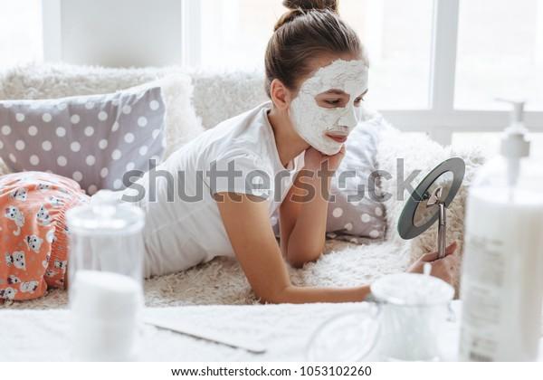 12歳の少女がソファーでくつろぎ、粘土の顔のマスクを作る。肌の汚れを防ぐ10代の女の子。朝のスキンケアの日課。