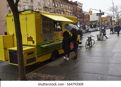 1/20/2017 Brooklyn Ny, A mother and daughter wait for a food truck while it rains in Brooklyn NY.