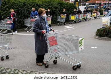 12/03/2020 Paina, Monza Brianza, Lombardy, Italy.  - Coronavirus COVID-19 pandemic. People with facial masks and gloves queuing for quota entrance in the supermarket.