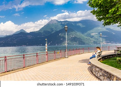 12.06. 2019 Italy, Europe: European girl sitting on the waterfront and exploring the sights in the vicinity of Varenna. Beautiful view the high mountains and shore lake Como in summer sunny day