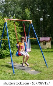 12.06.2014 Russia, Kaliningrad. Teen rides a swing out in the Park and jumps off them.