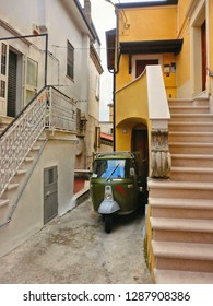 12.08.2016. Matera, Basilicata Italy - vintage green Ape Car on the old narrow street with facade of houses and steps in South Italy