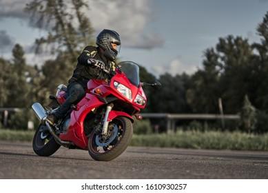 12-08-2019 Riga, Latvia. Man in black motorcycle jacket and black helmet ride on red sport motorcycle. Man driving motorcycle