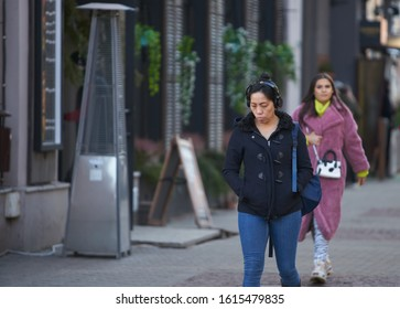 12-10-2018 RIga, Latvia Beautiful girl with headphones walking on streets of old town