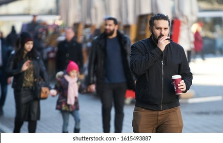 12-10-2018 Riga, Latvia Man in jacket drinks coffee from paper cup and smokes cigar