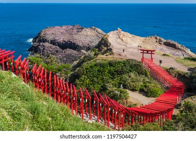 The 123 red torii gates of Motonosumi Inari Shrine curve down the hillside to a rock formation on the north coast of Yamaguchi with the Sea of Japan in the background
